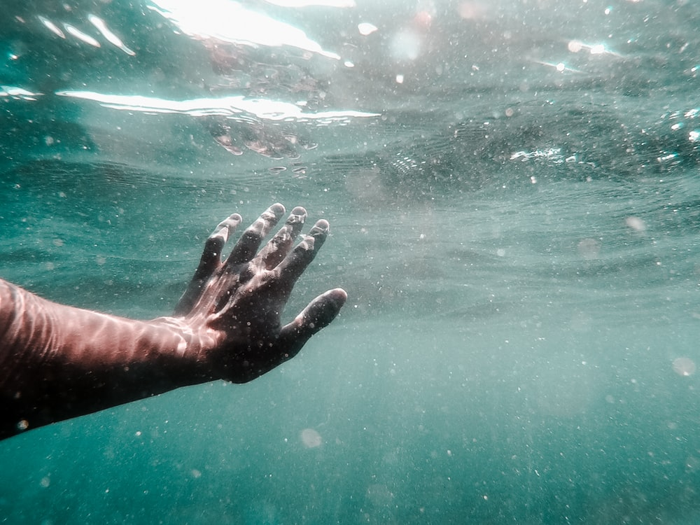 human left hand on body of water