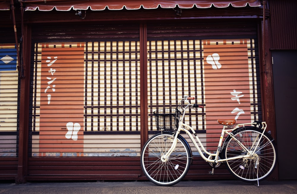 white beach bicycle beside brown and white painted house