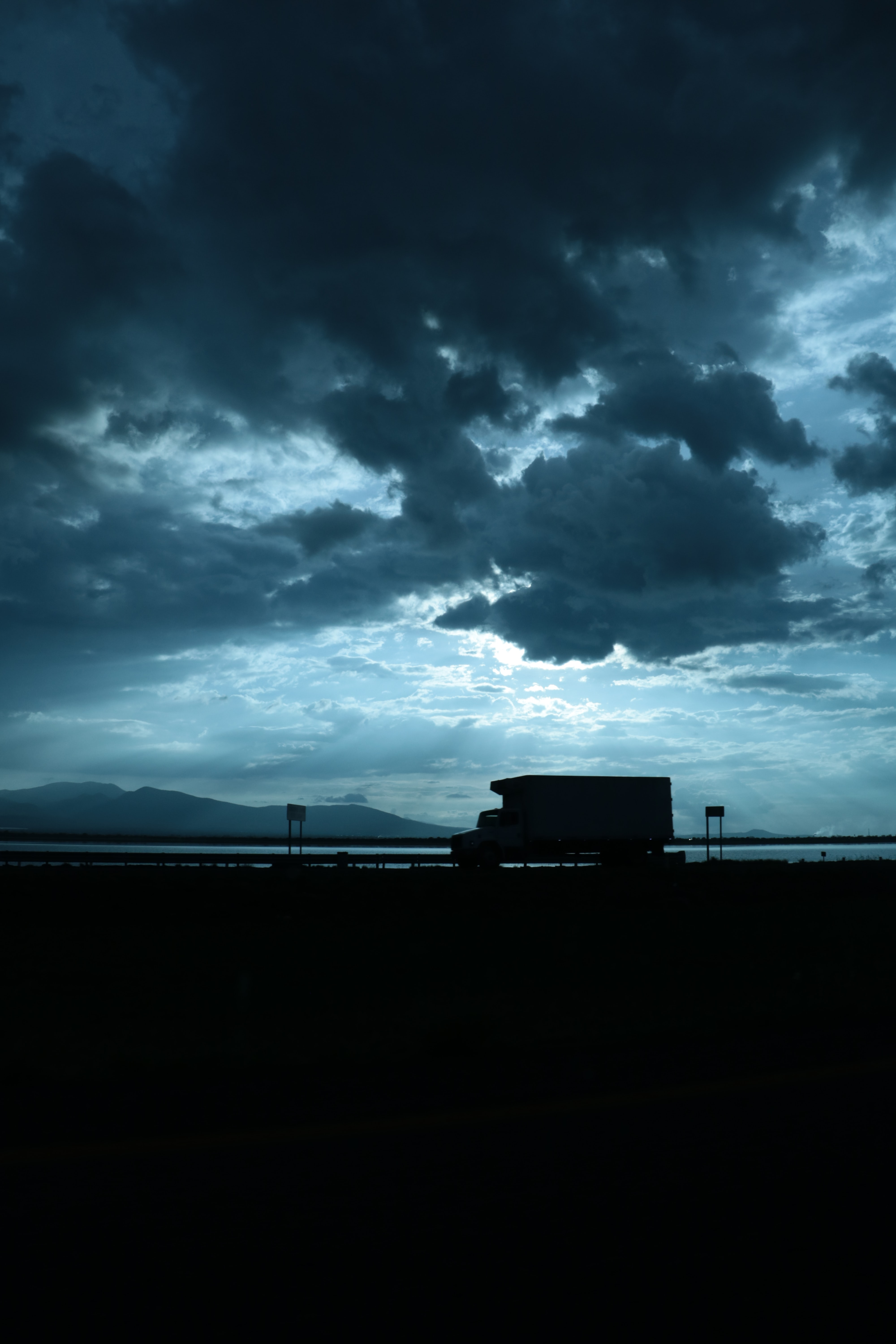 silhouette of car passing through road with cloudy sky