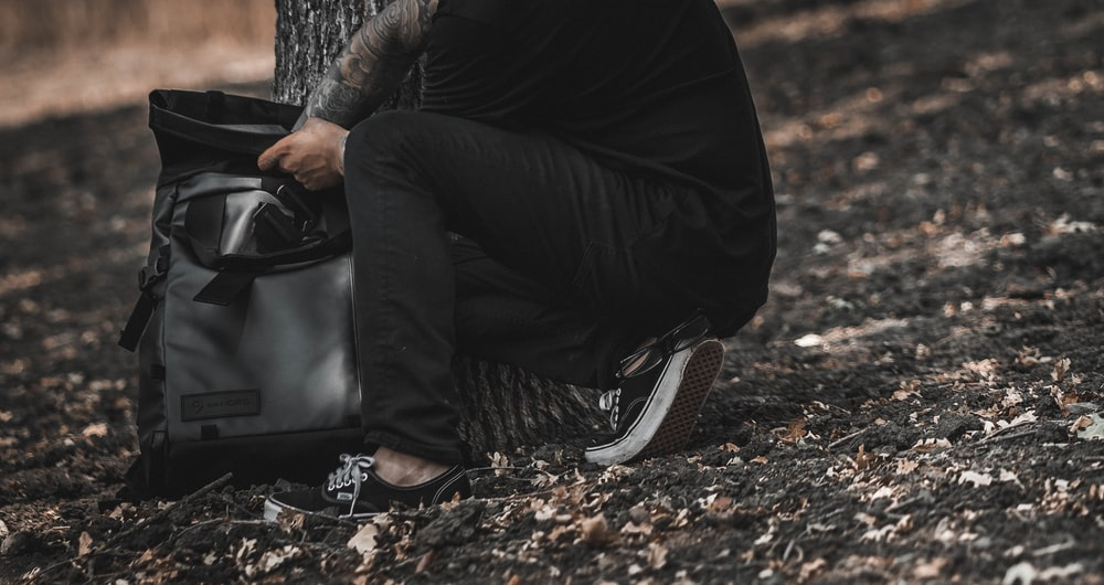 person holding gray and black backpack