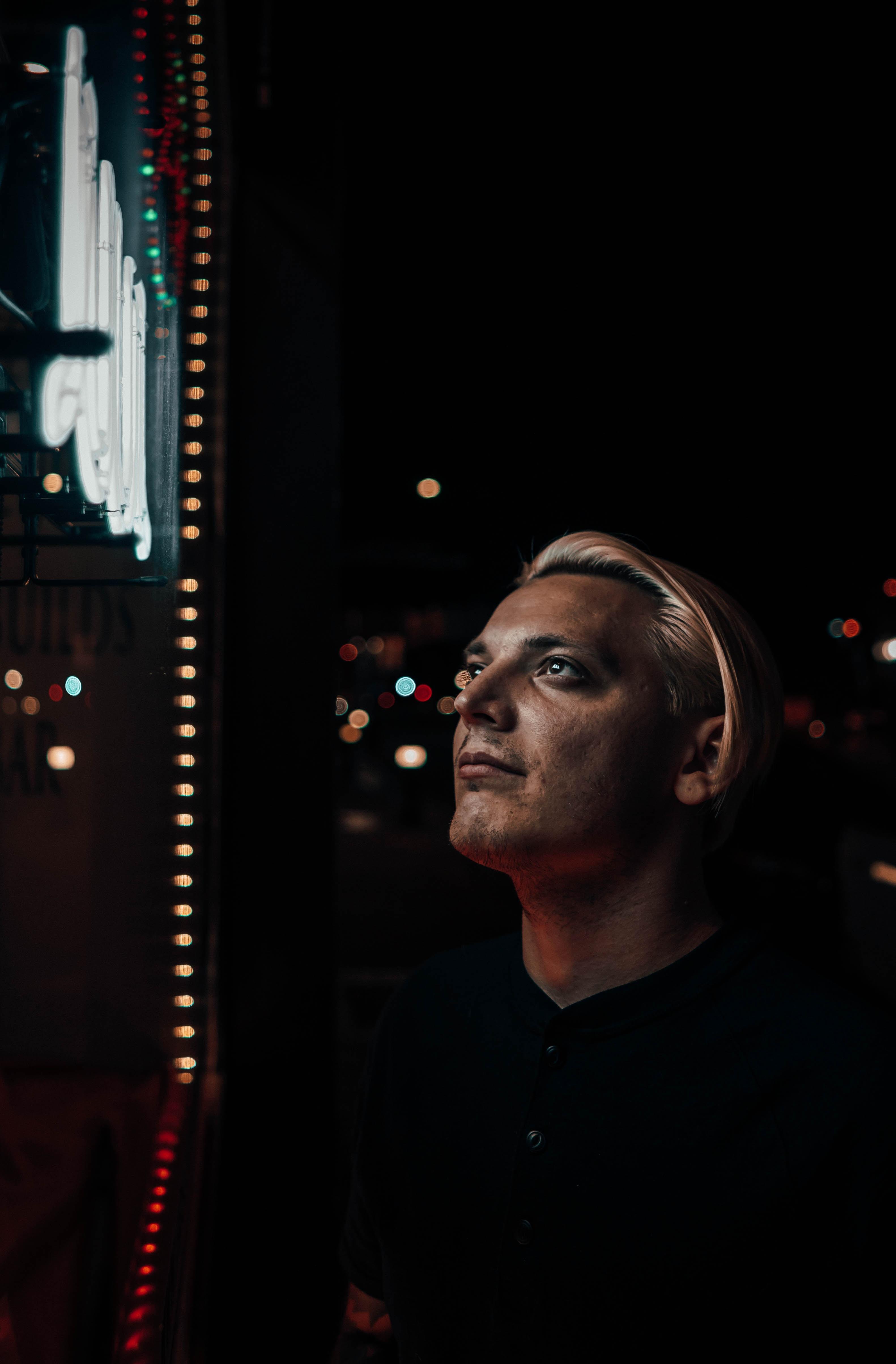 man staring at lighted signage