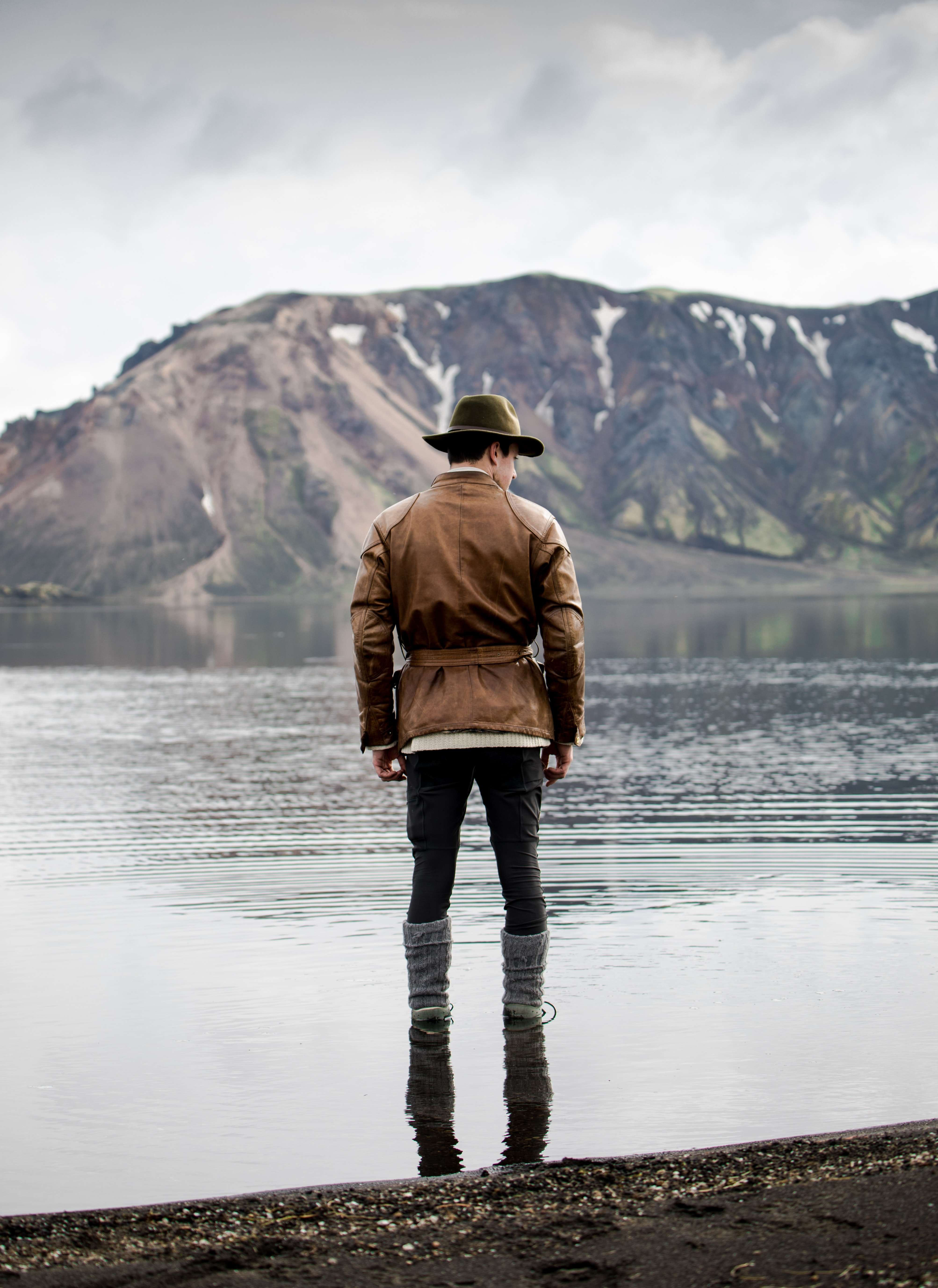 man standing in body of water facing toward mountain