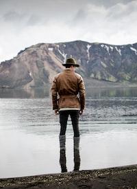 man standing in body of water facing toward mountain