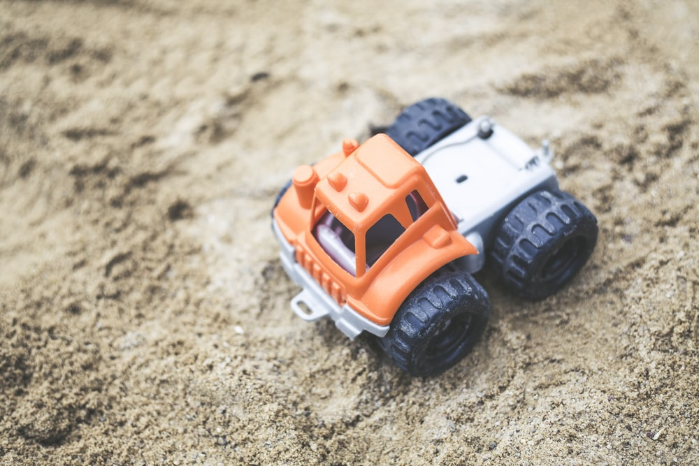 shallow focus photography of orange truck plastic toy on sand