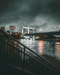grayscale photo of lighted bridge at night time