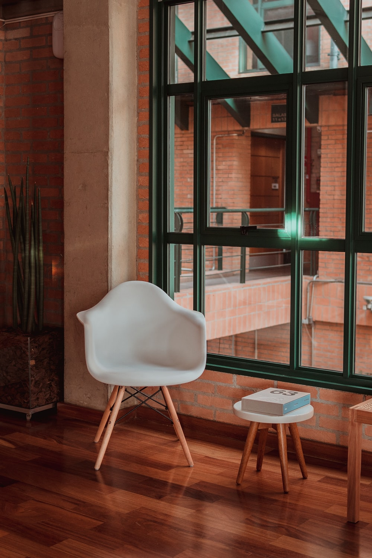 white armchair near glass window