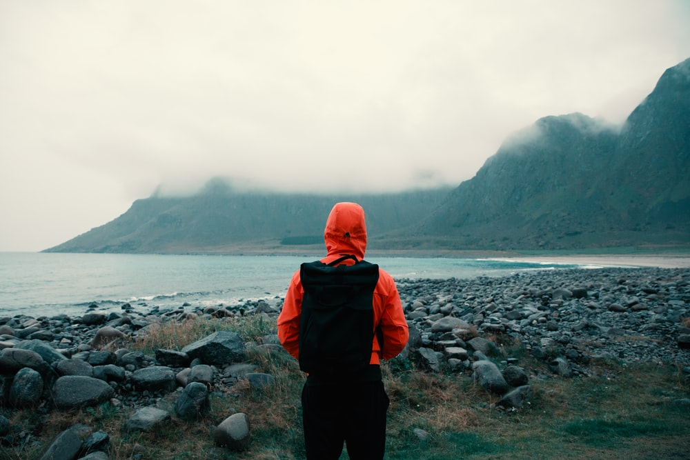 person in orange hooded jacket carrying bag looking at mountains coated with fogs