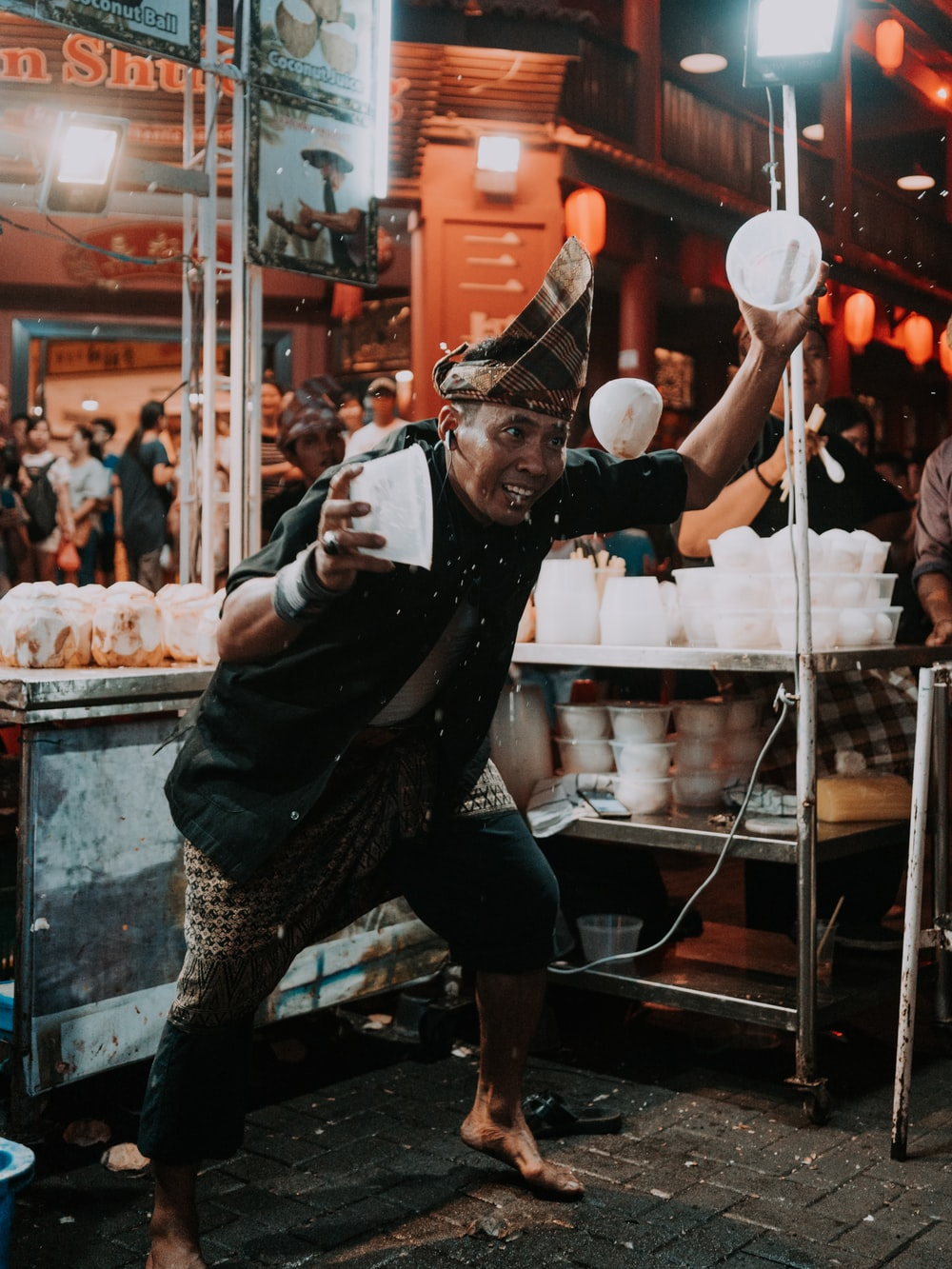 man holding two white plastic bowls near food stall