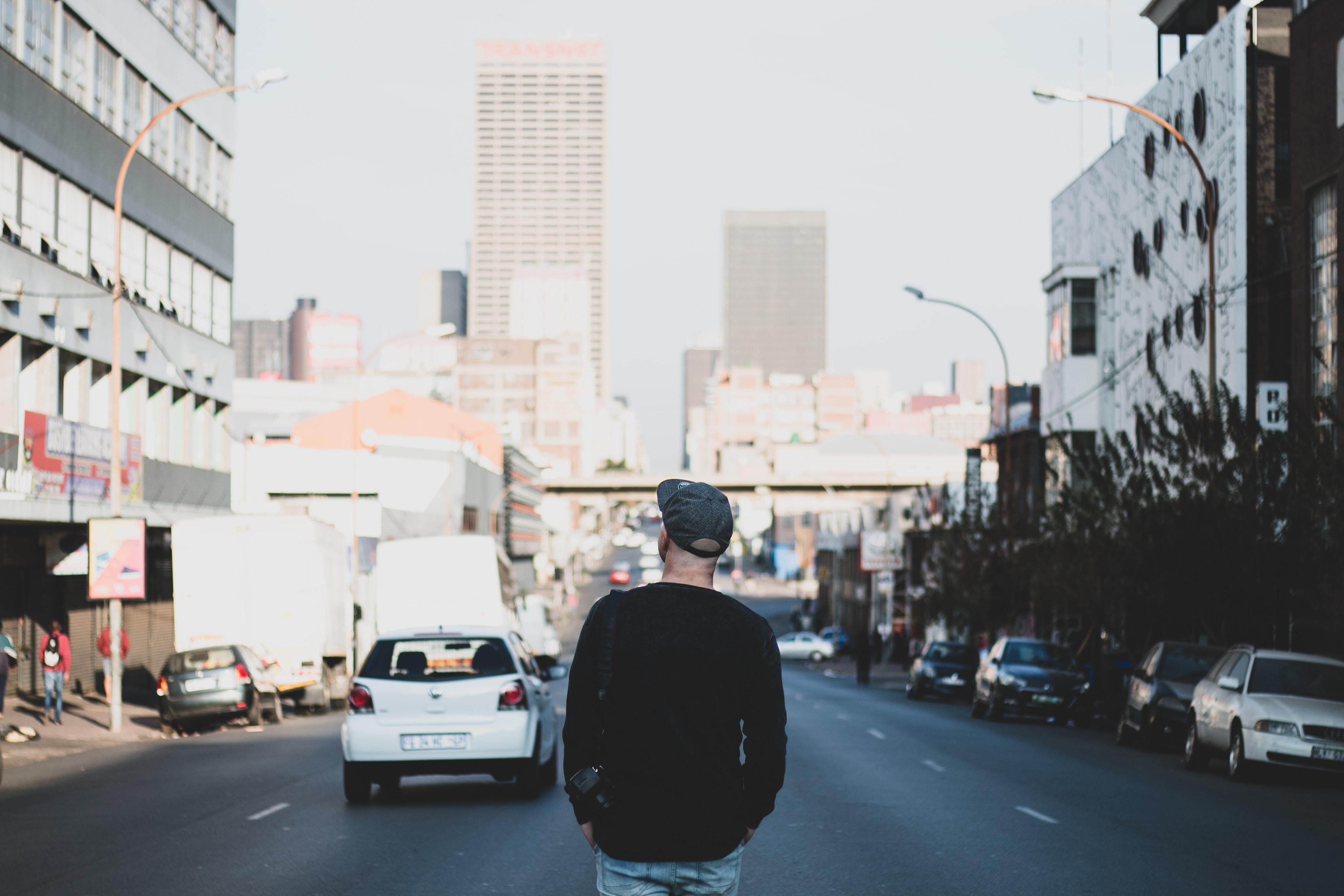 man standing in between road