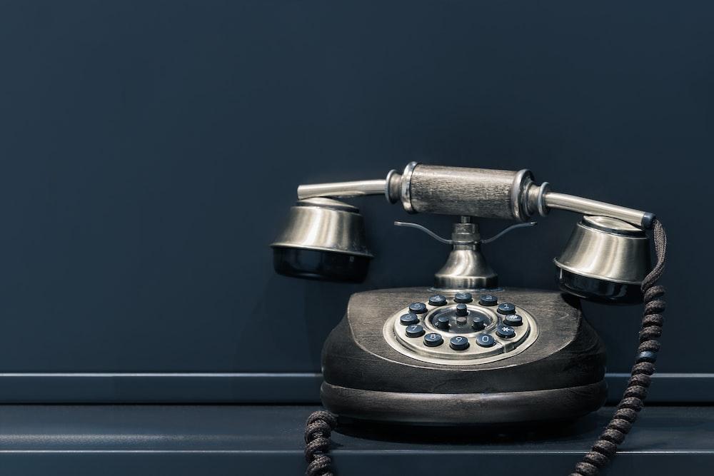 black and brown rotary phone near gray wall