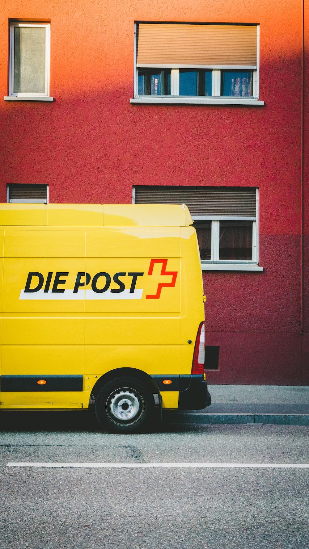 yellow Die Post+ van park beside road