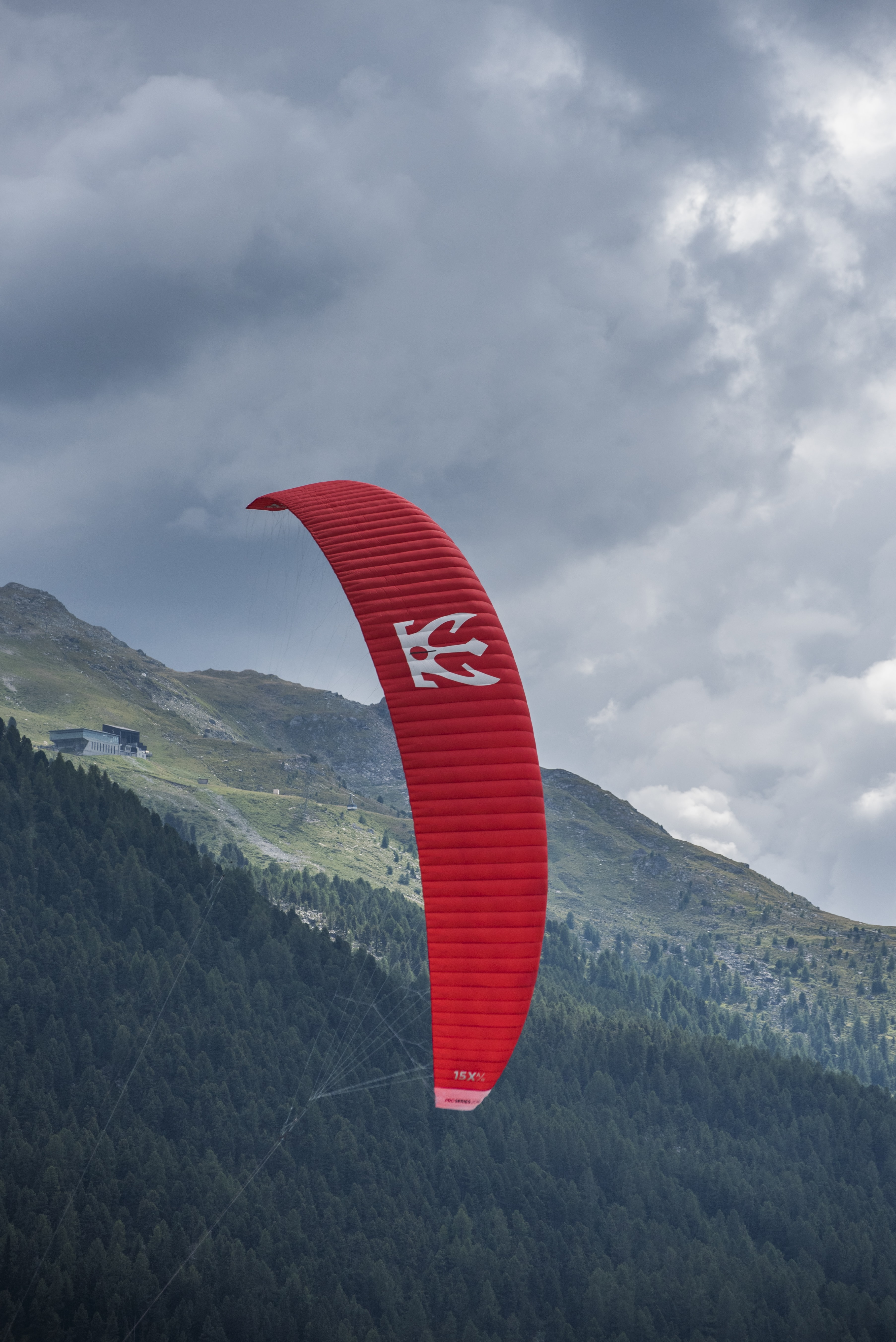 person riding red parachute at daytime