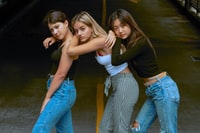 three women wearing assorted-color tops and pants