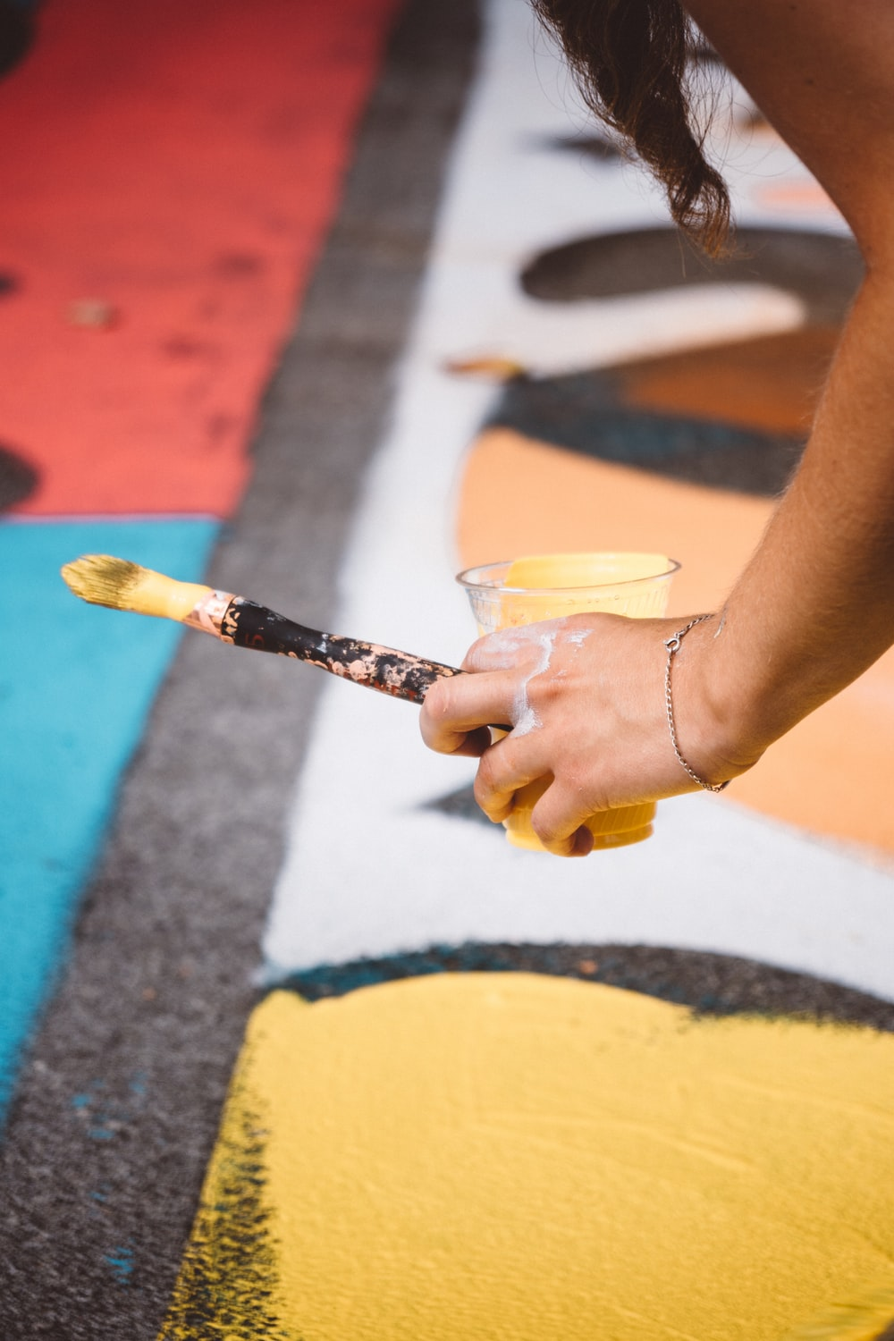 person holding cup with yellow paint and paintbrush