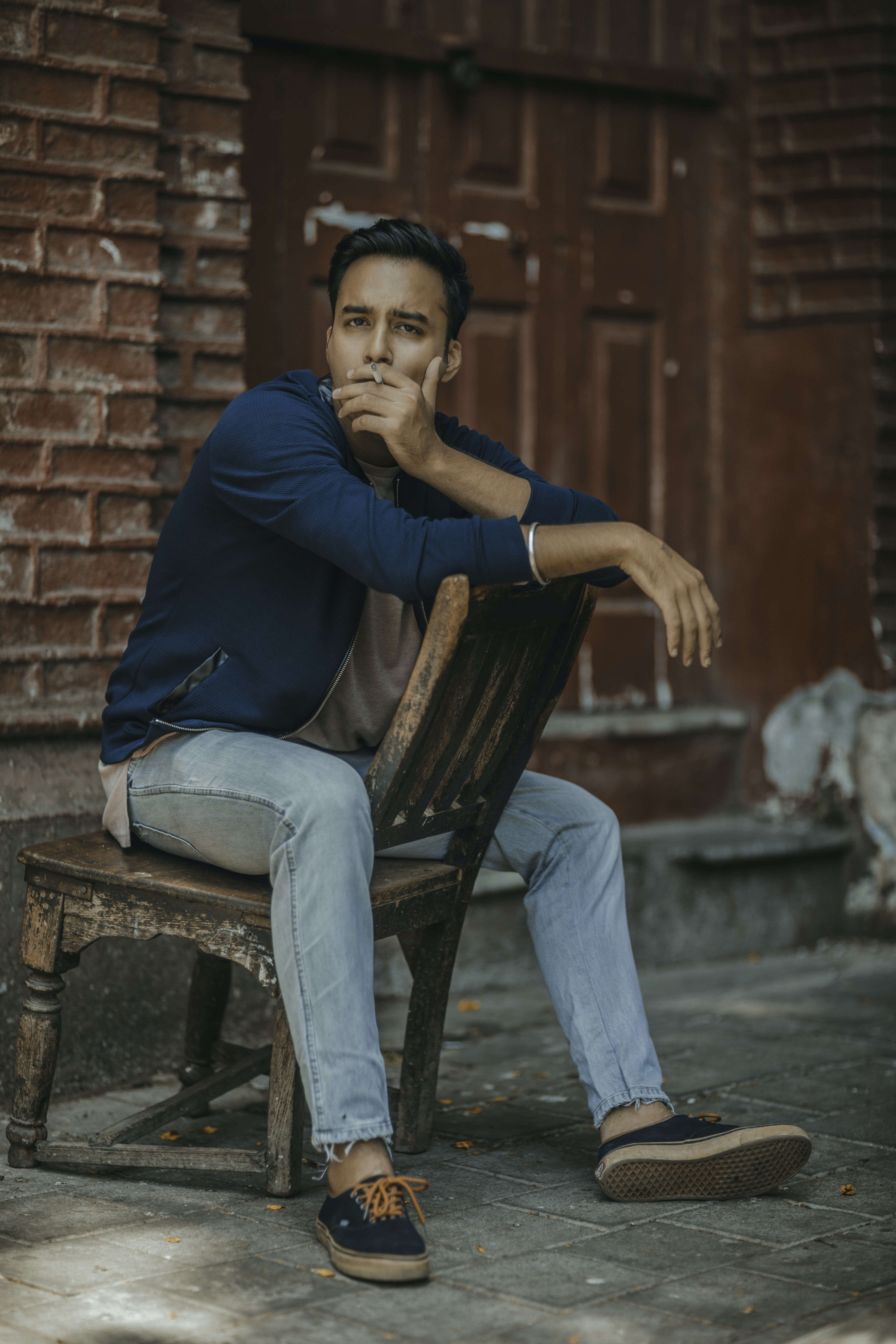 man in blue jacket smoking while sitting on chair near building
