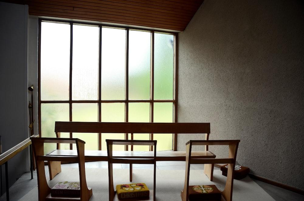 brown wooden chair near glass window