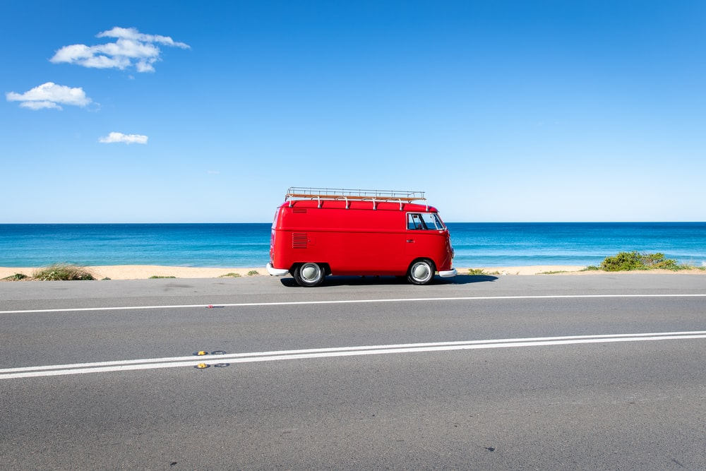 red van on asphalt road near the seashore