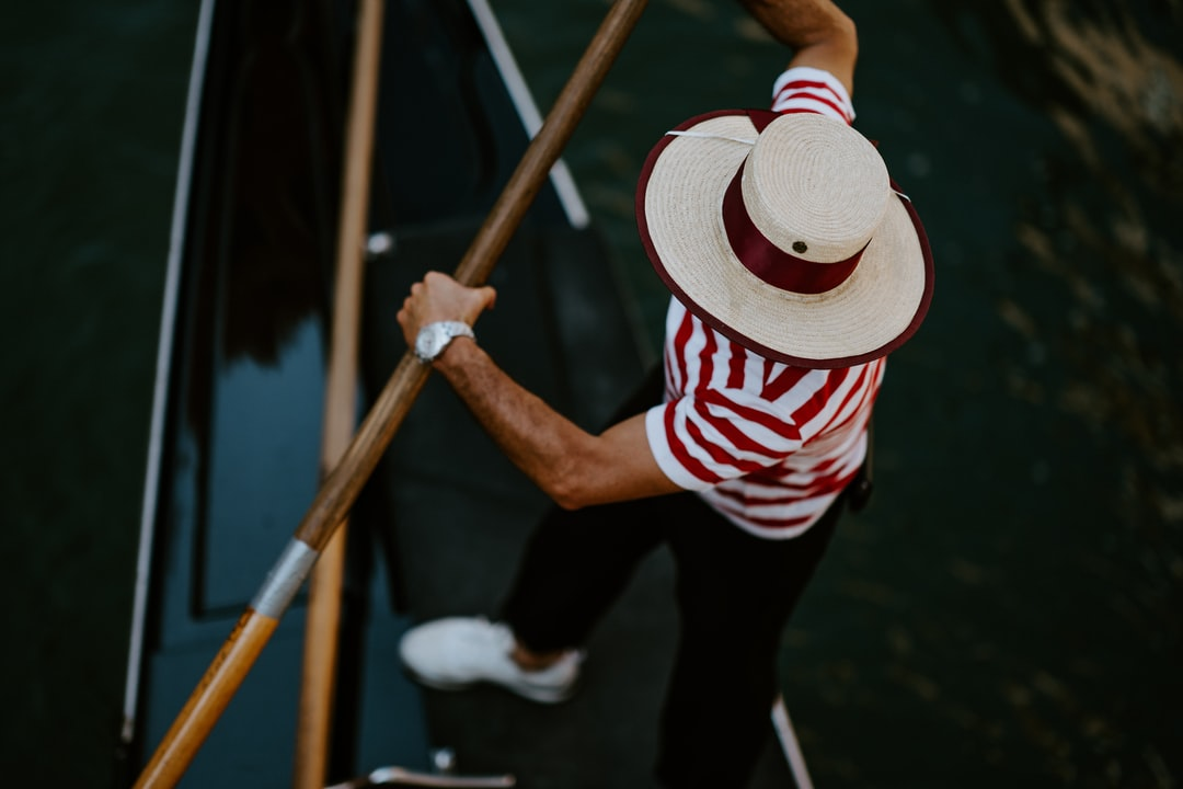 Faceless Venetian gondolier rowing