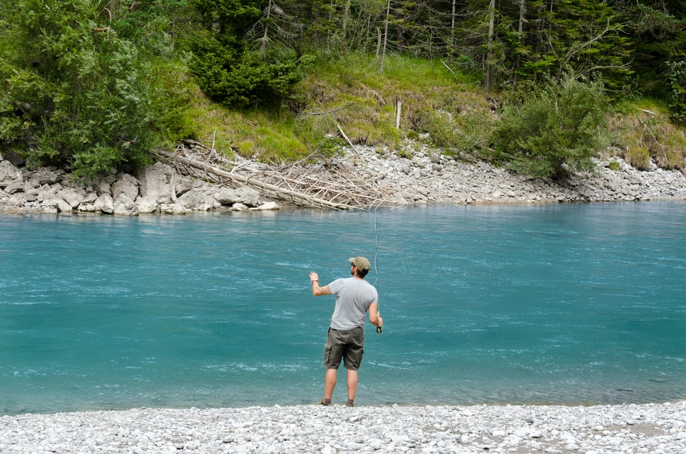 man holding fishing rod in front of body of water
