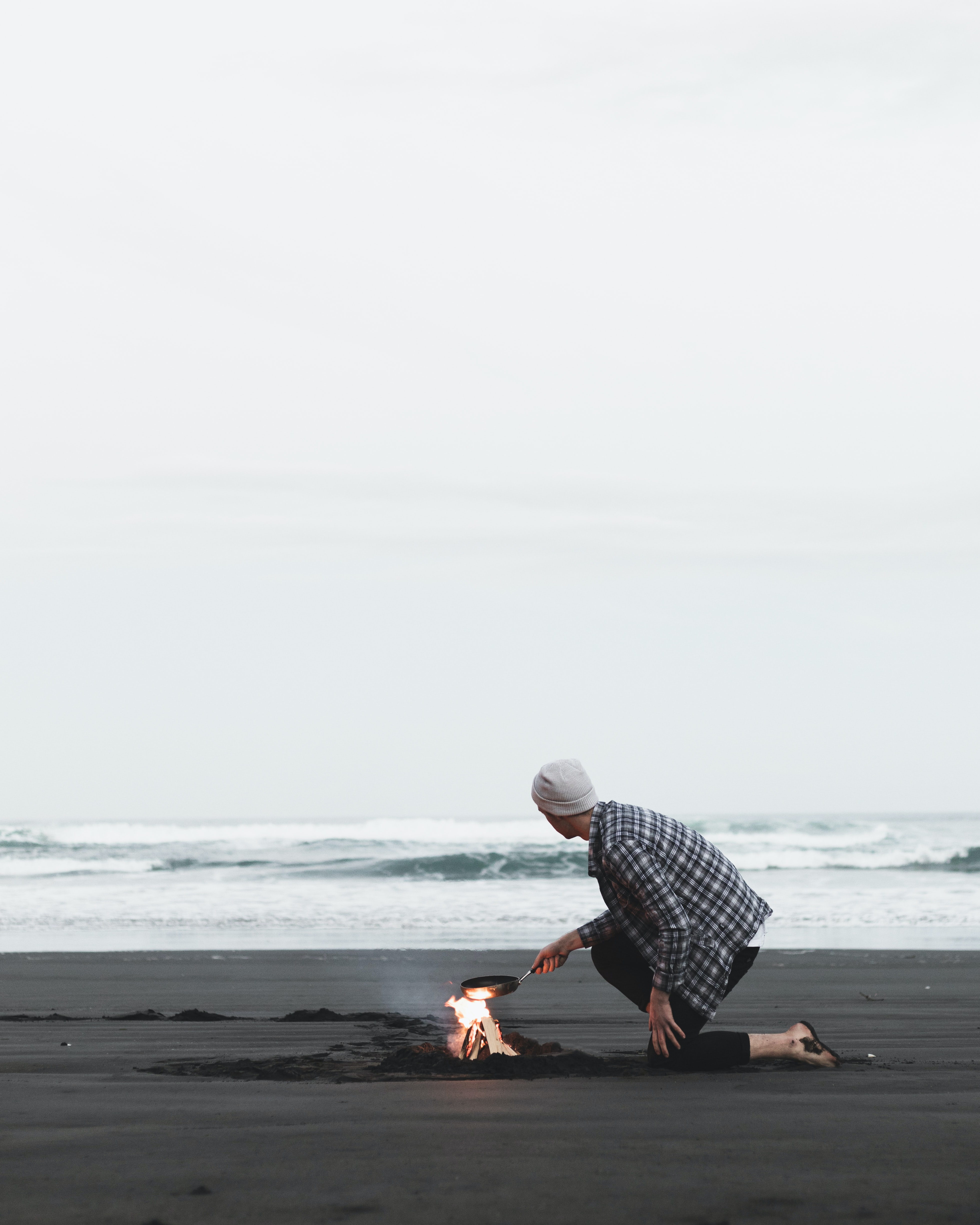 person cooking on seashore