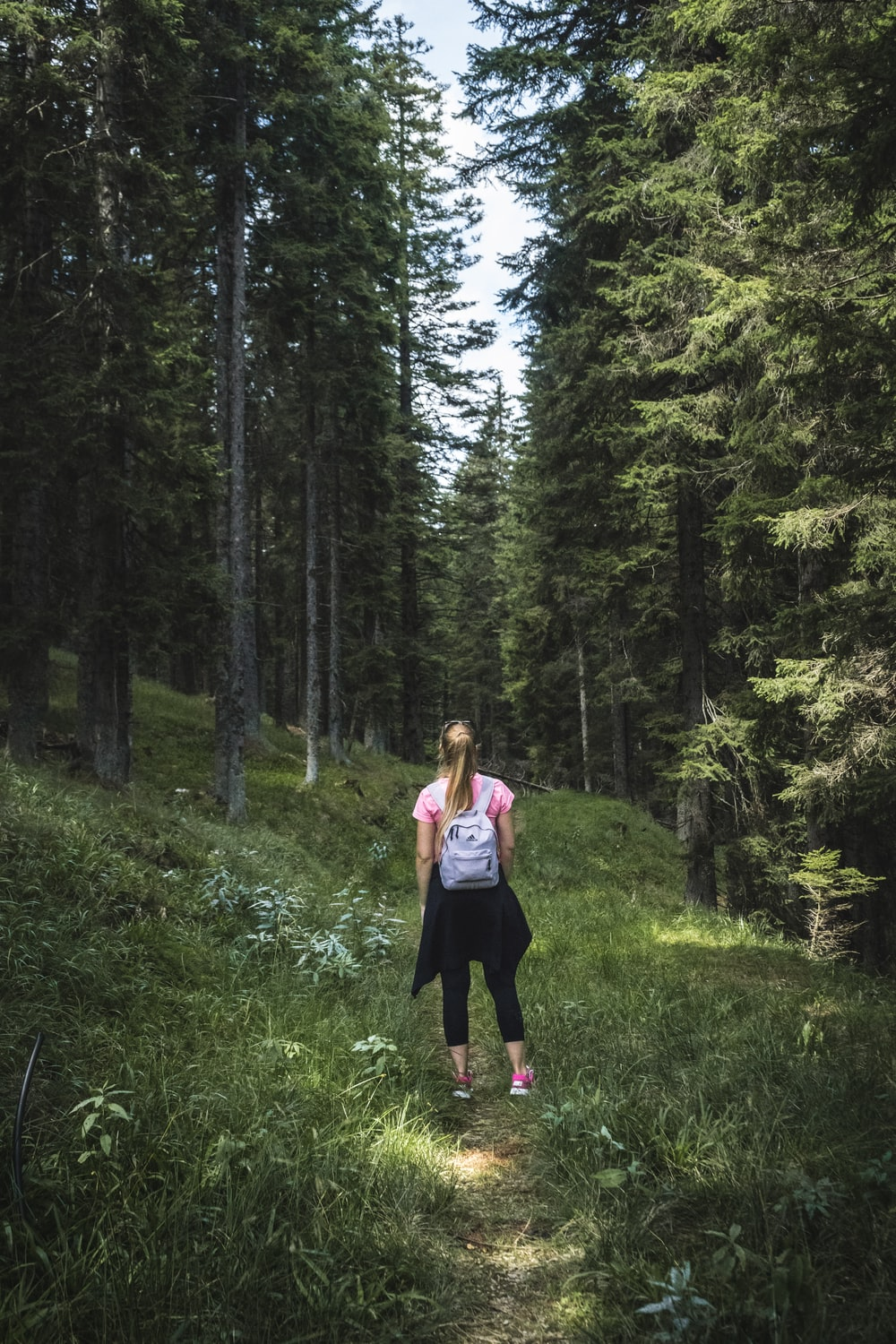 woman carrying backpack on forest
