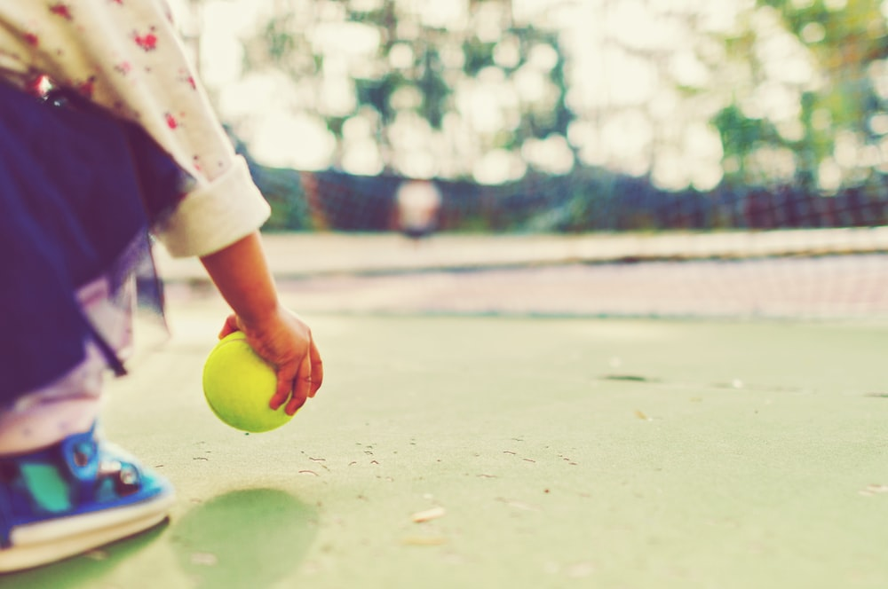 kid holding tennis ball in front of goal net