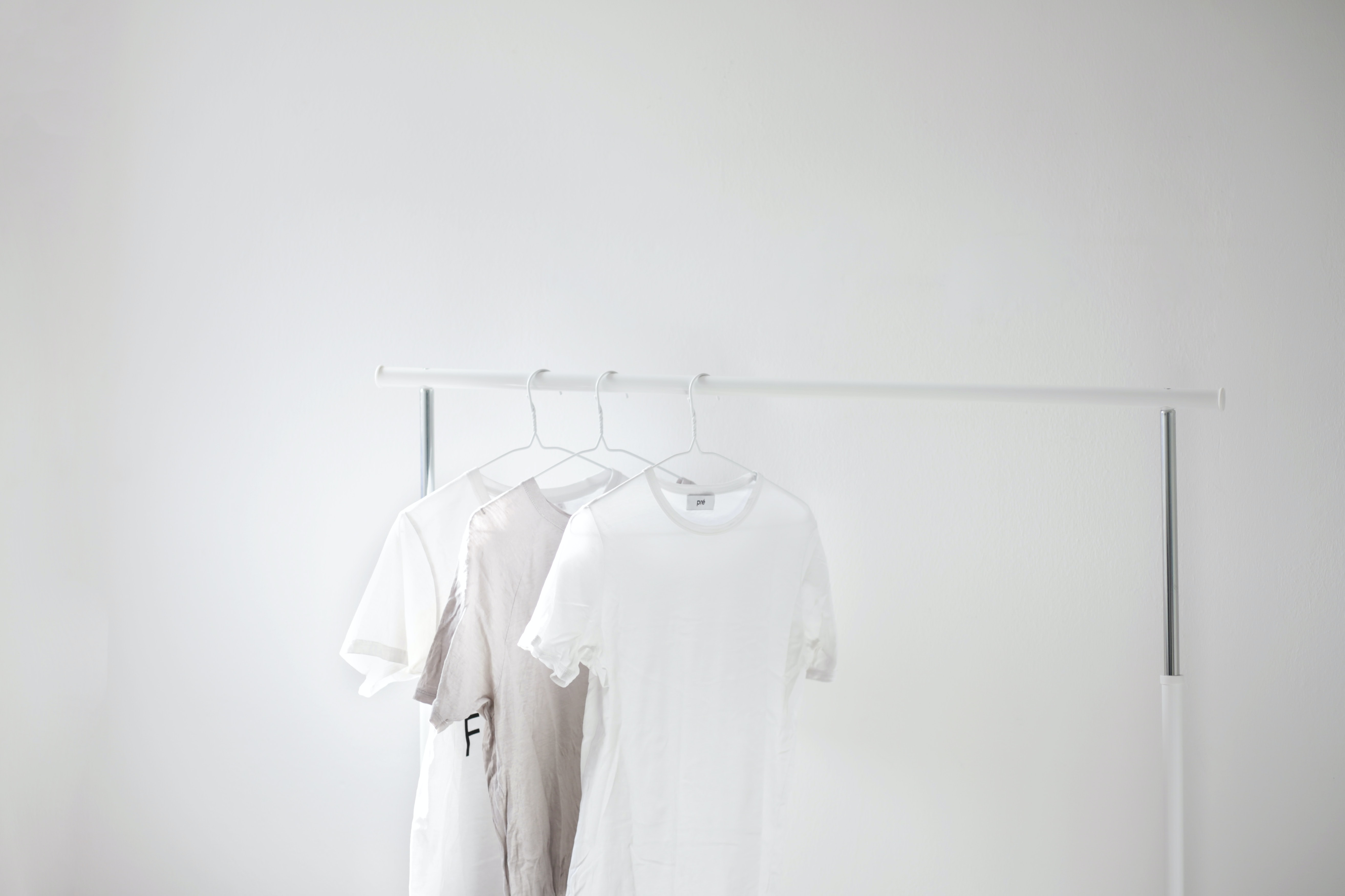 three gray and white crew-neck t-shirts on cloth drying rack