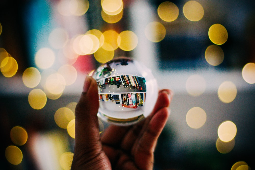 person holding clear crystal ball with bokeh background photography