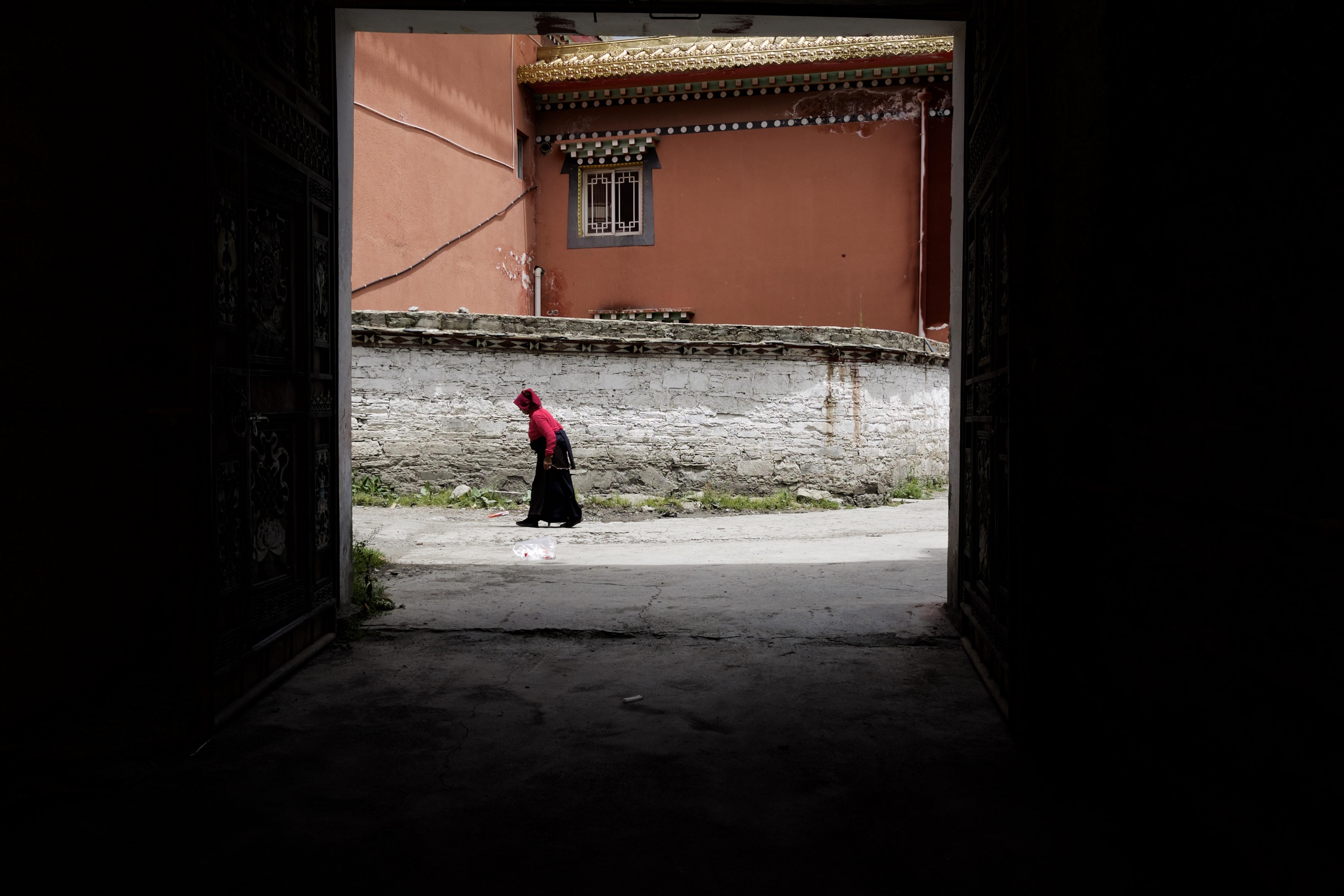 person walking near orange building