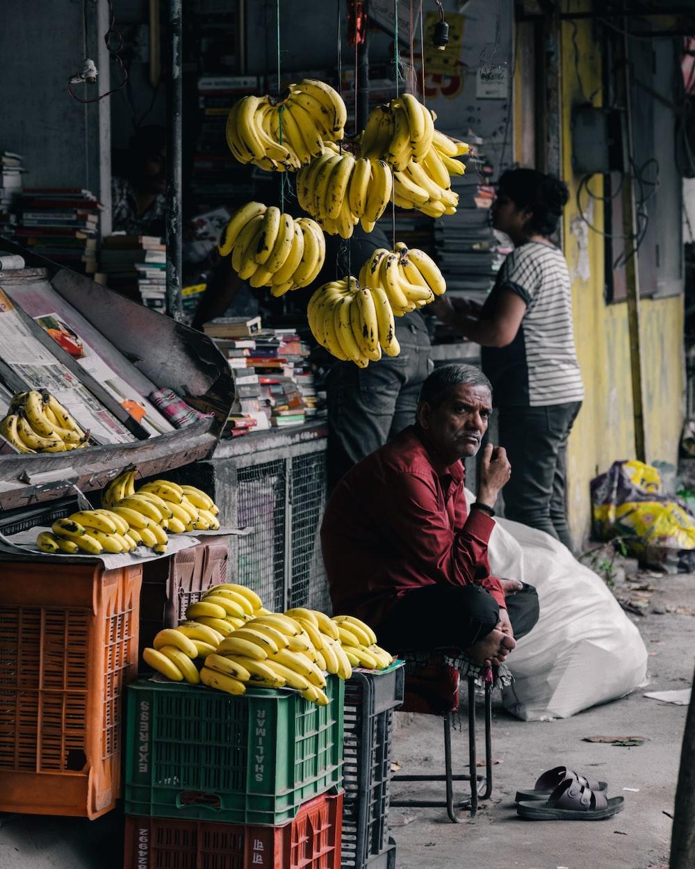 man sitting on chair near bananas