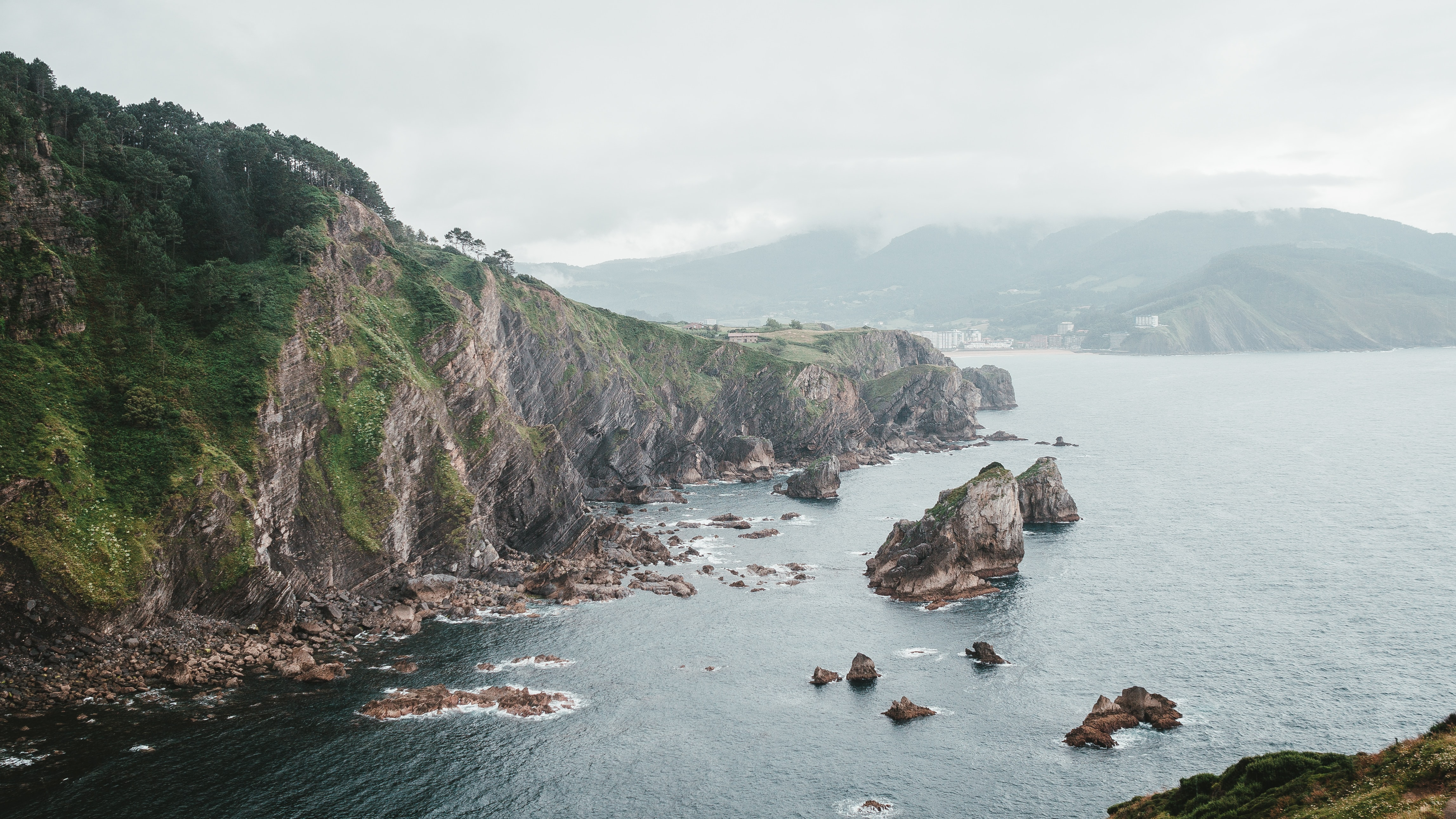 panoramic photography of rock formation near body of water