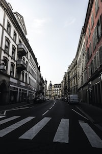 concrete road between white and red buildings
