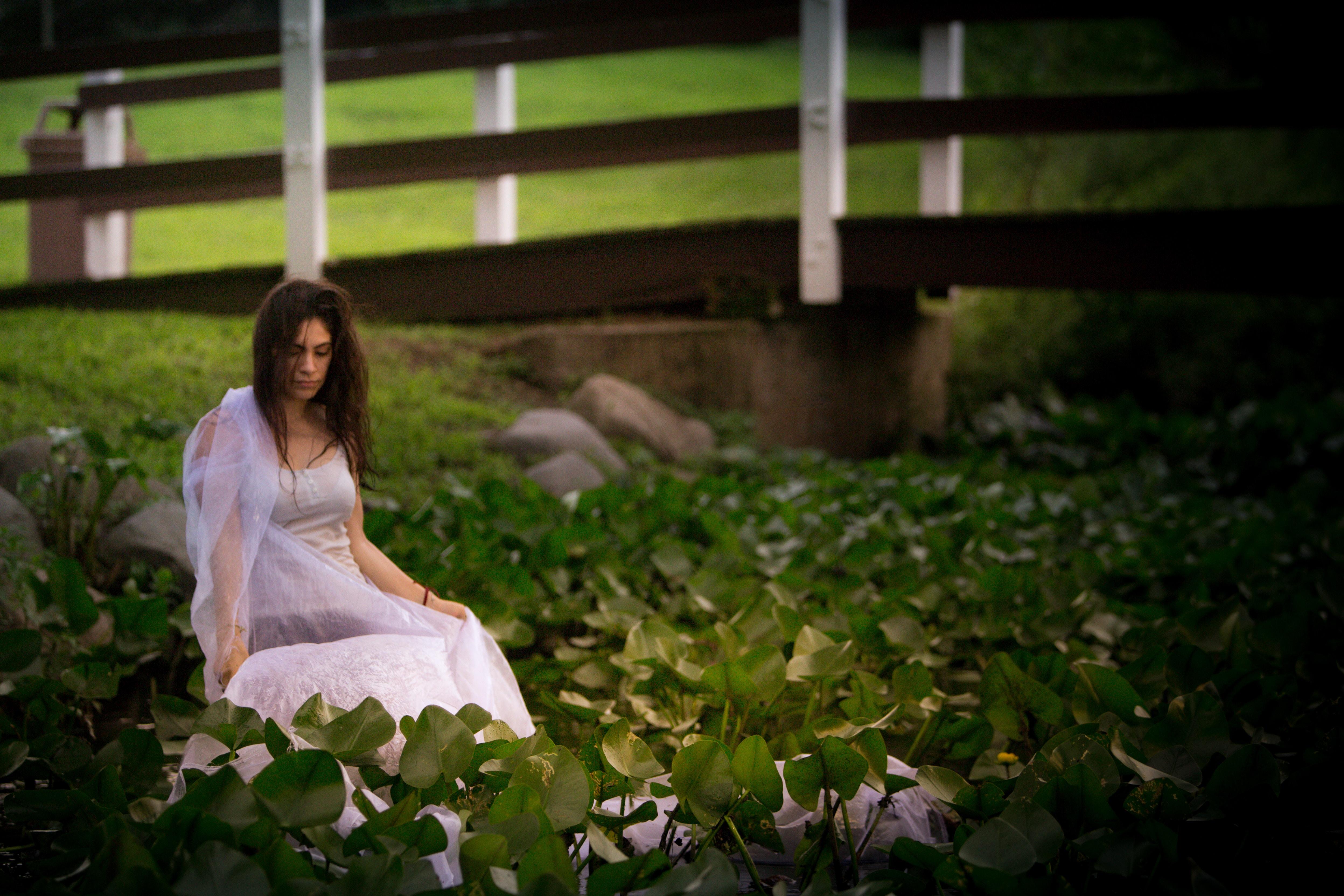 woman in white dress sitting beside plants