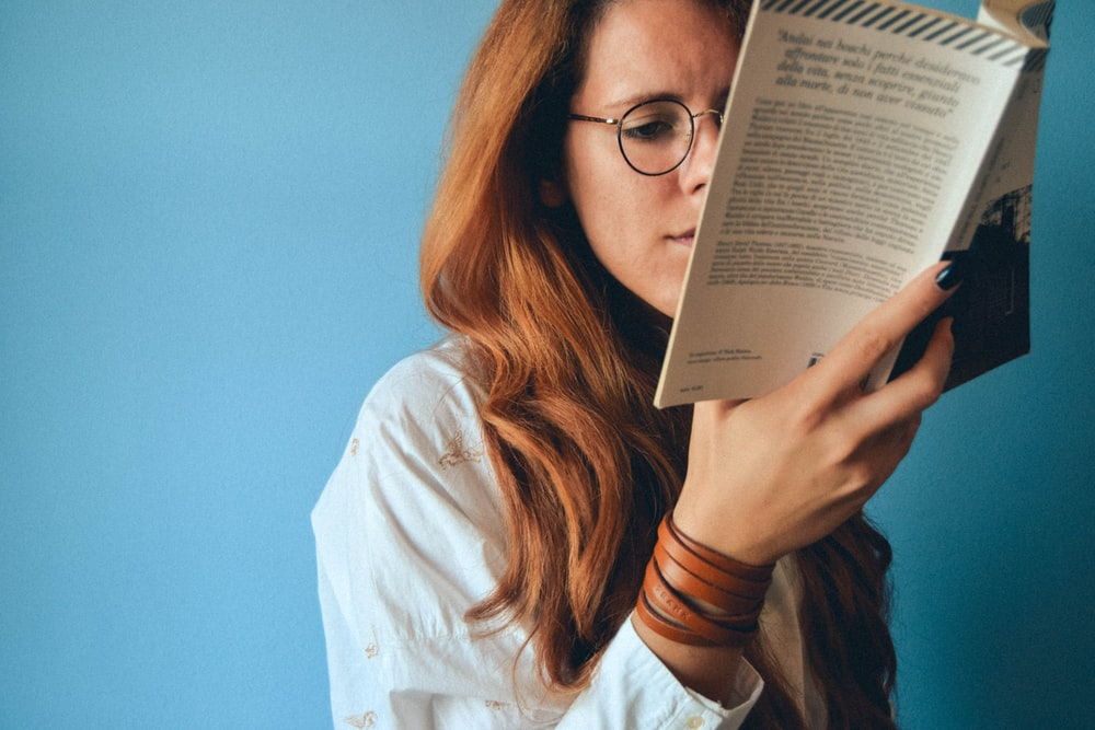 woman wearing eyeglasses holding a book