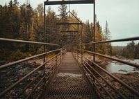 brown metal bridge above rocky river architectural photography at daytime
