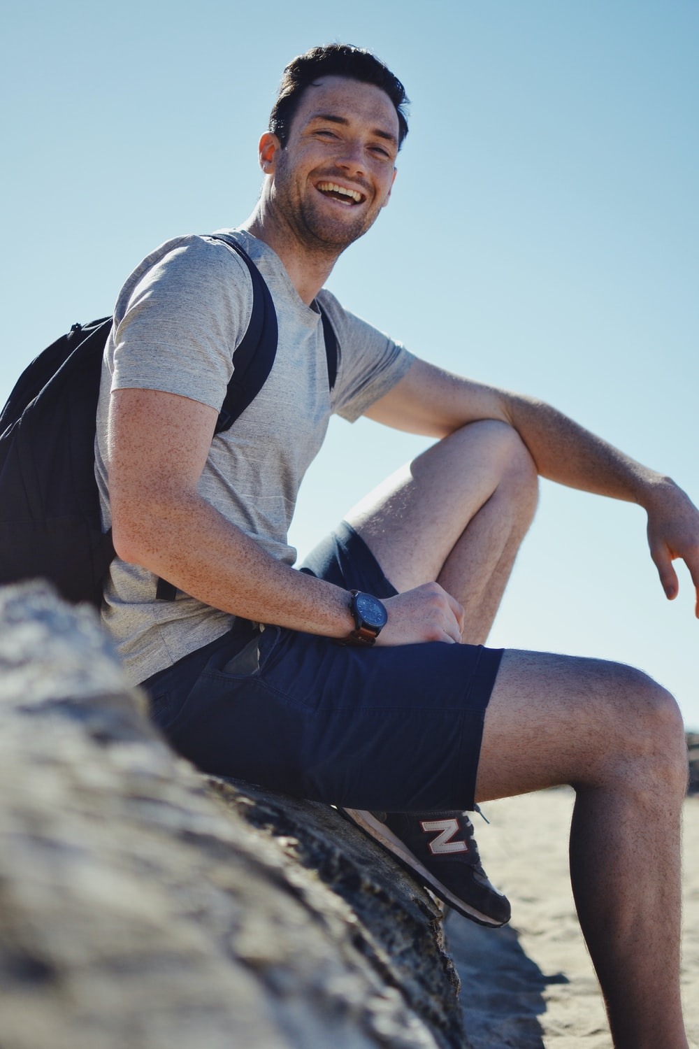 smiling man sitting on gray rock at daytime