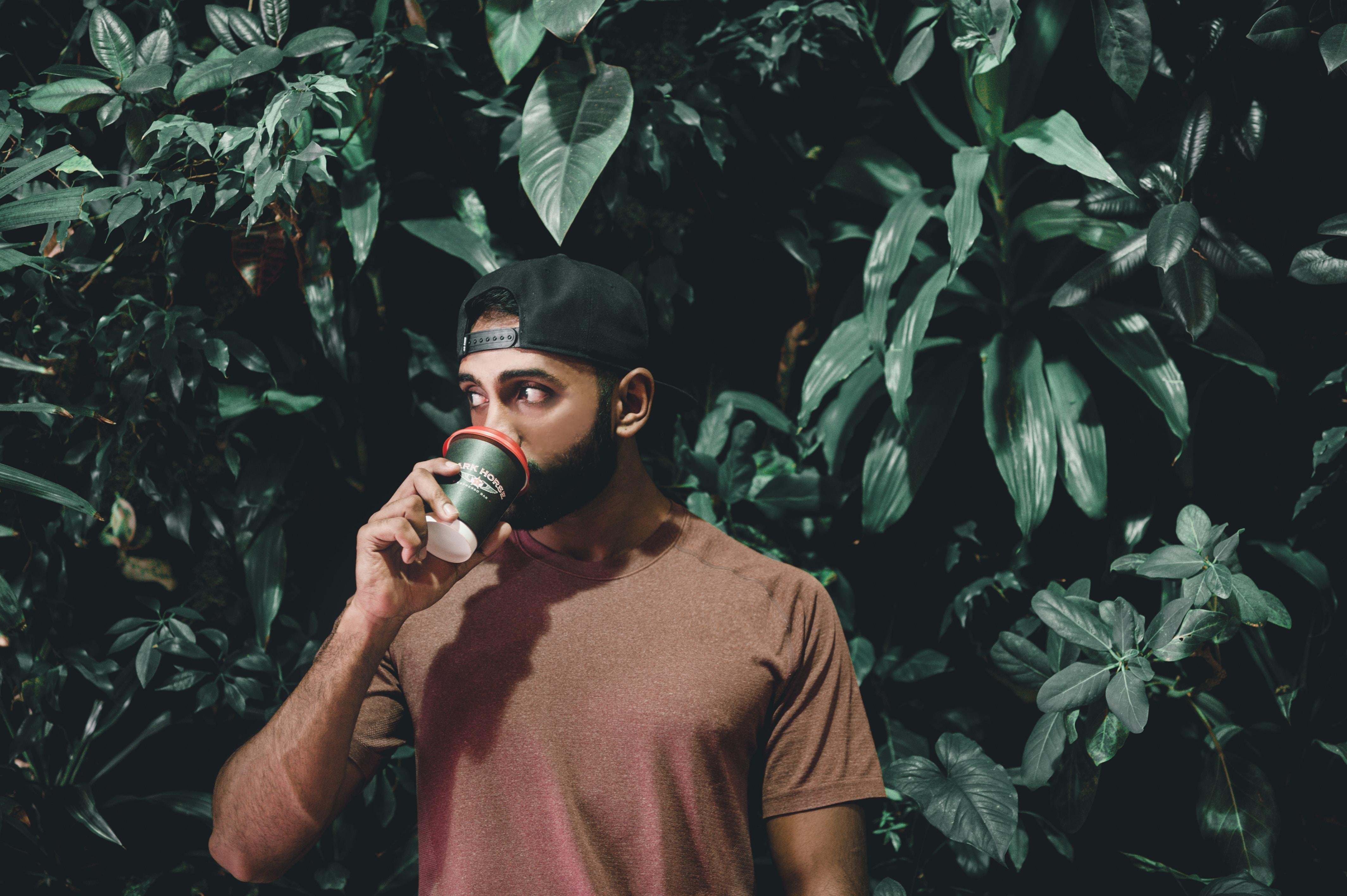 man drinking behind green leafed plnats