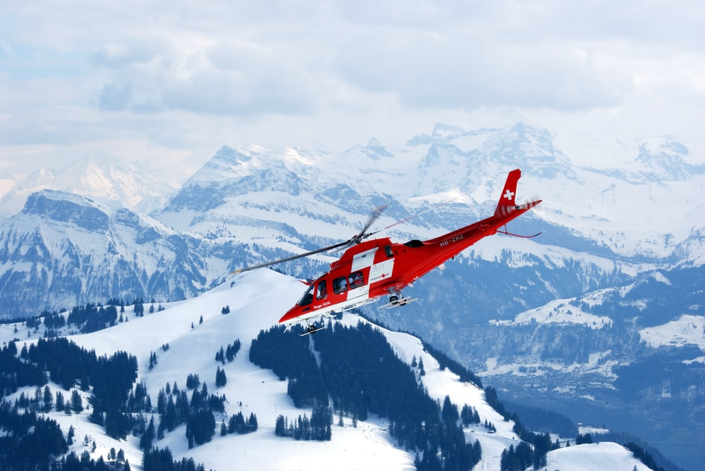 photo of flight of red and white rescue helicopter during snow daytime