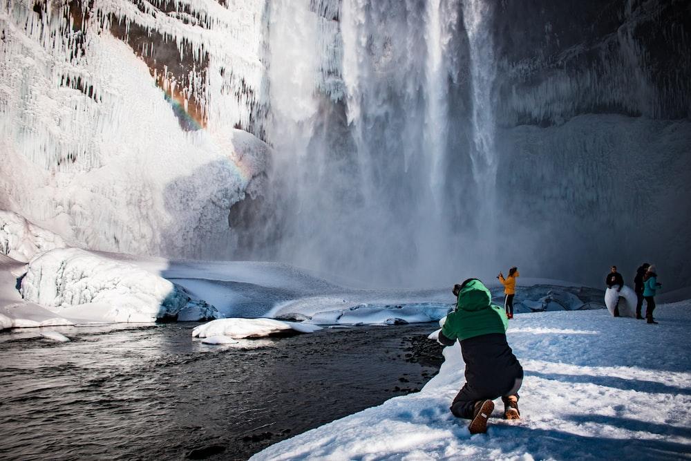 person kneeling beside body of water