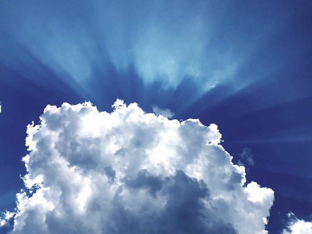 sun rays through white cumulus clouds