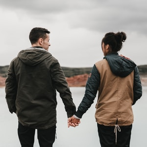 couple holding hand front of body of calm water with mountain distance