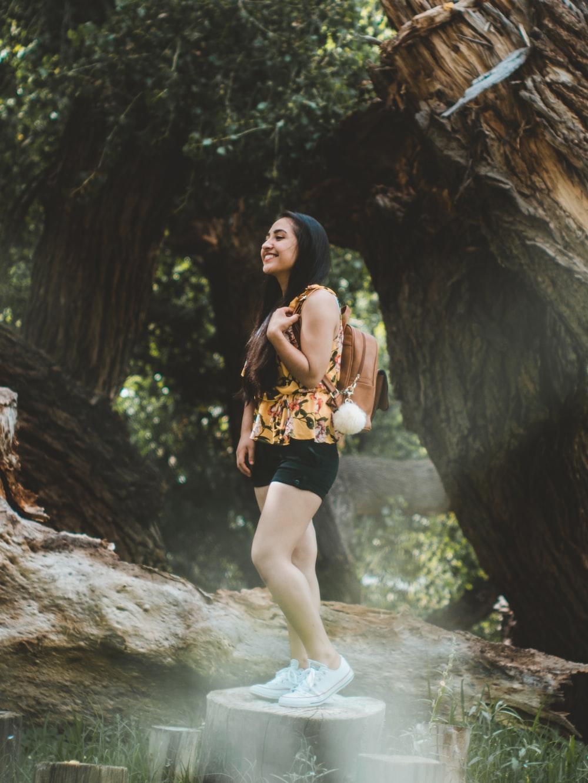 woman standing on tree trunk beside tree