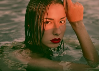 woman wearing red lipstick on body of water