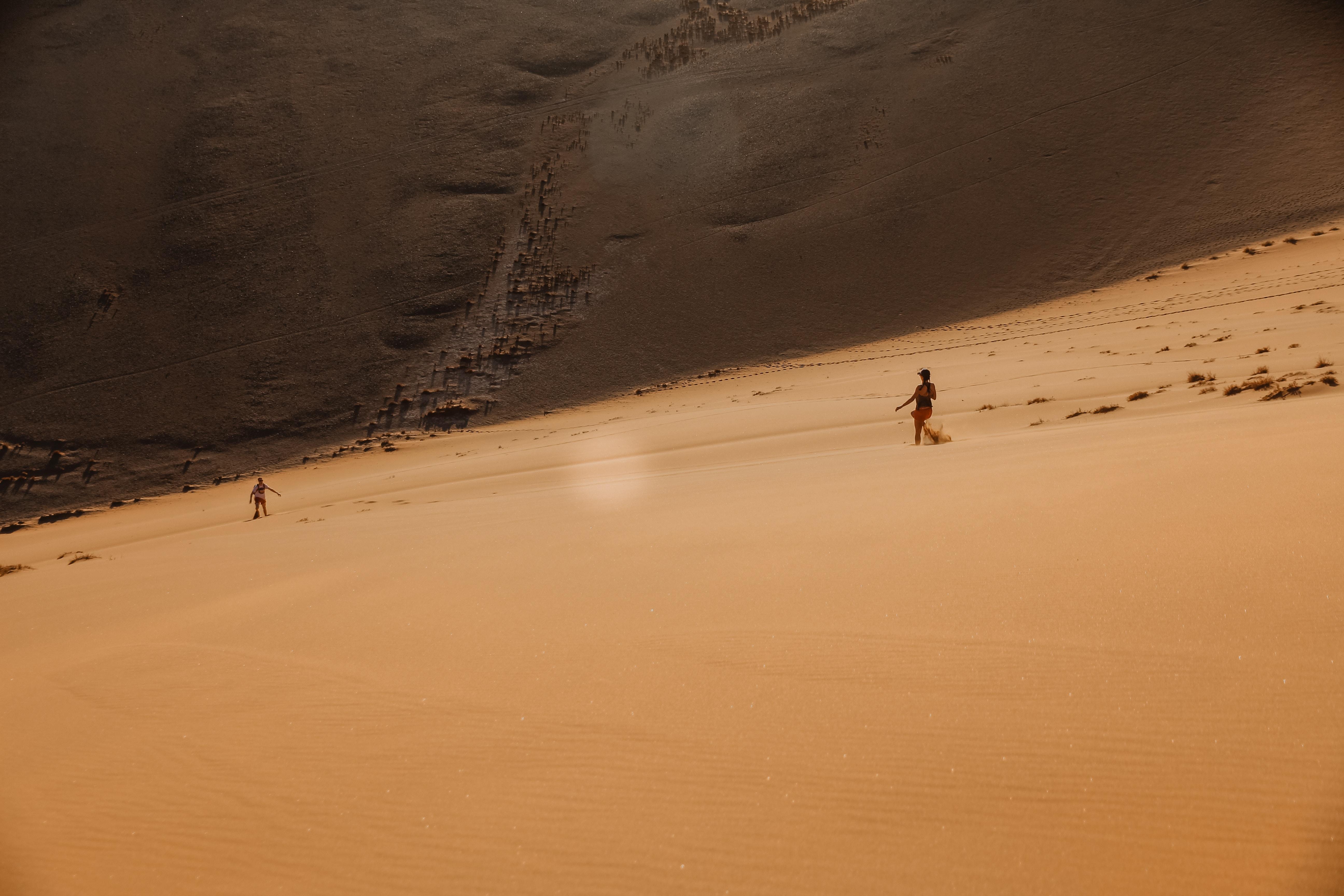 people walking on desert sand during daytime