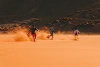 three men running on desert during daytime