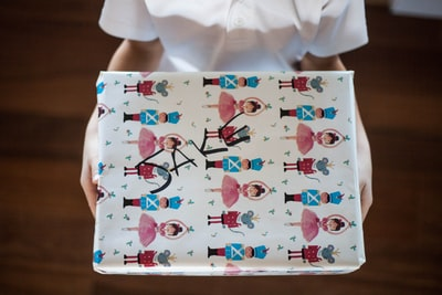 person holding illustration of woman and man wrapping paper teams background