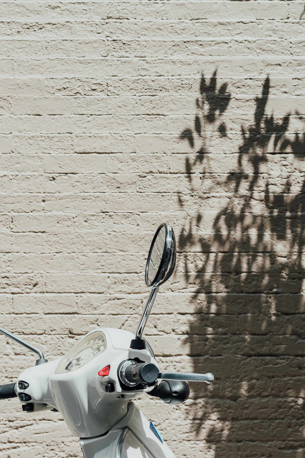 white motorcycle beside white wall during daytime