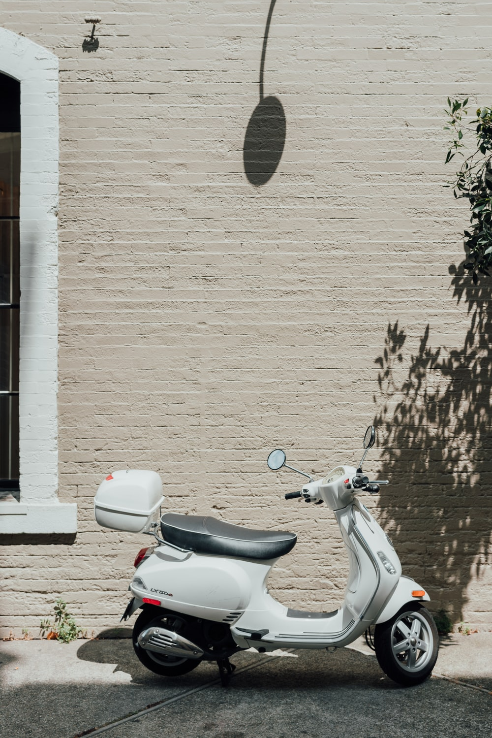 white and black motor scooter beside white wall