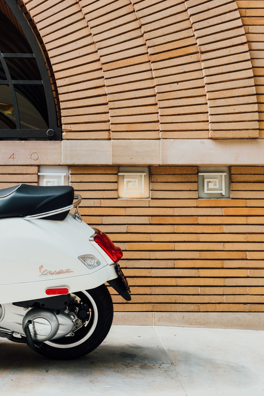 white motorcycle parked beside brown wall