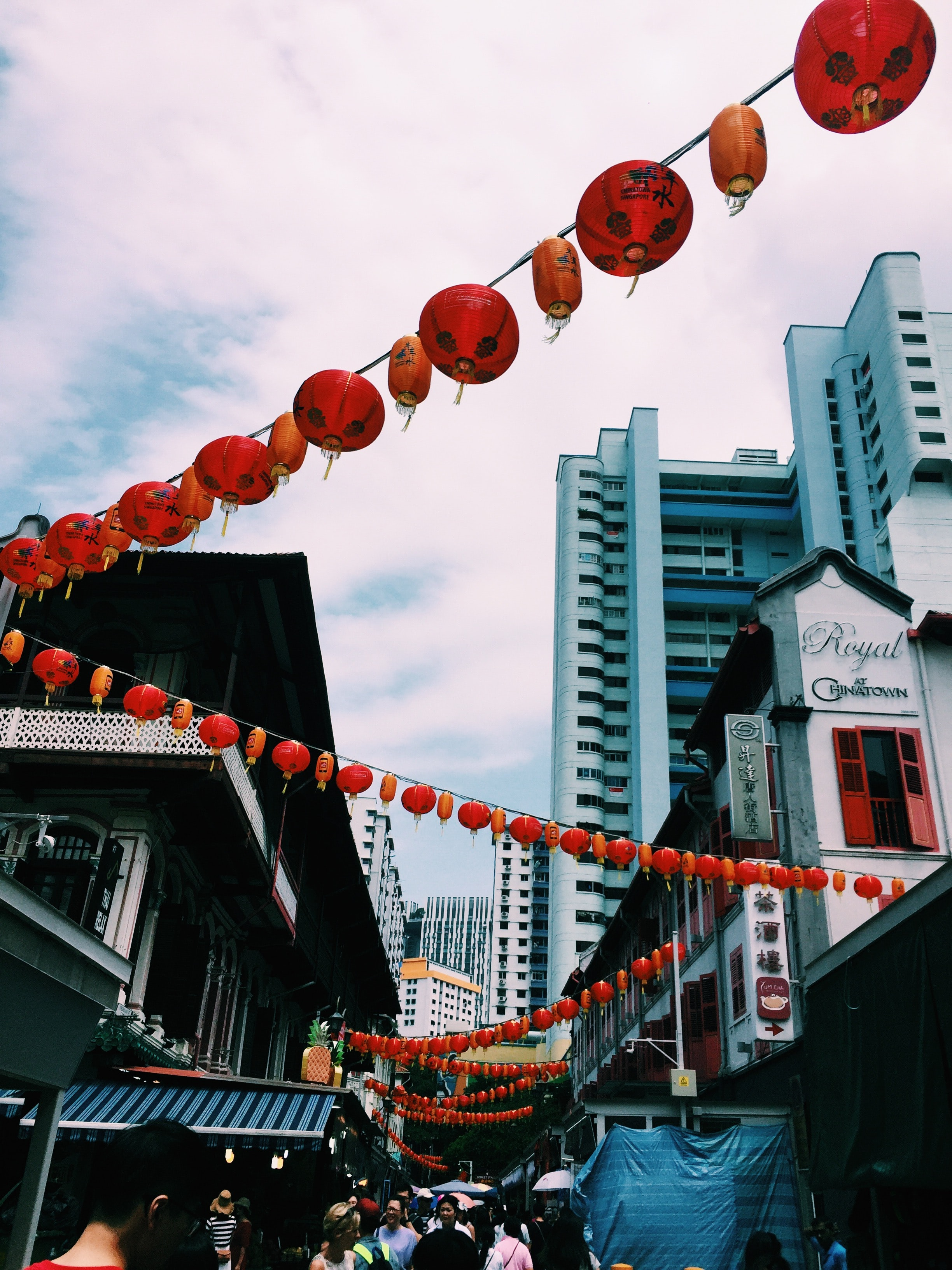 red and orange lanterns hanged above alleyway surrounded with group of people